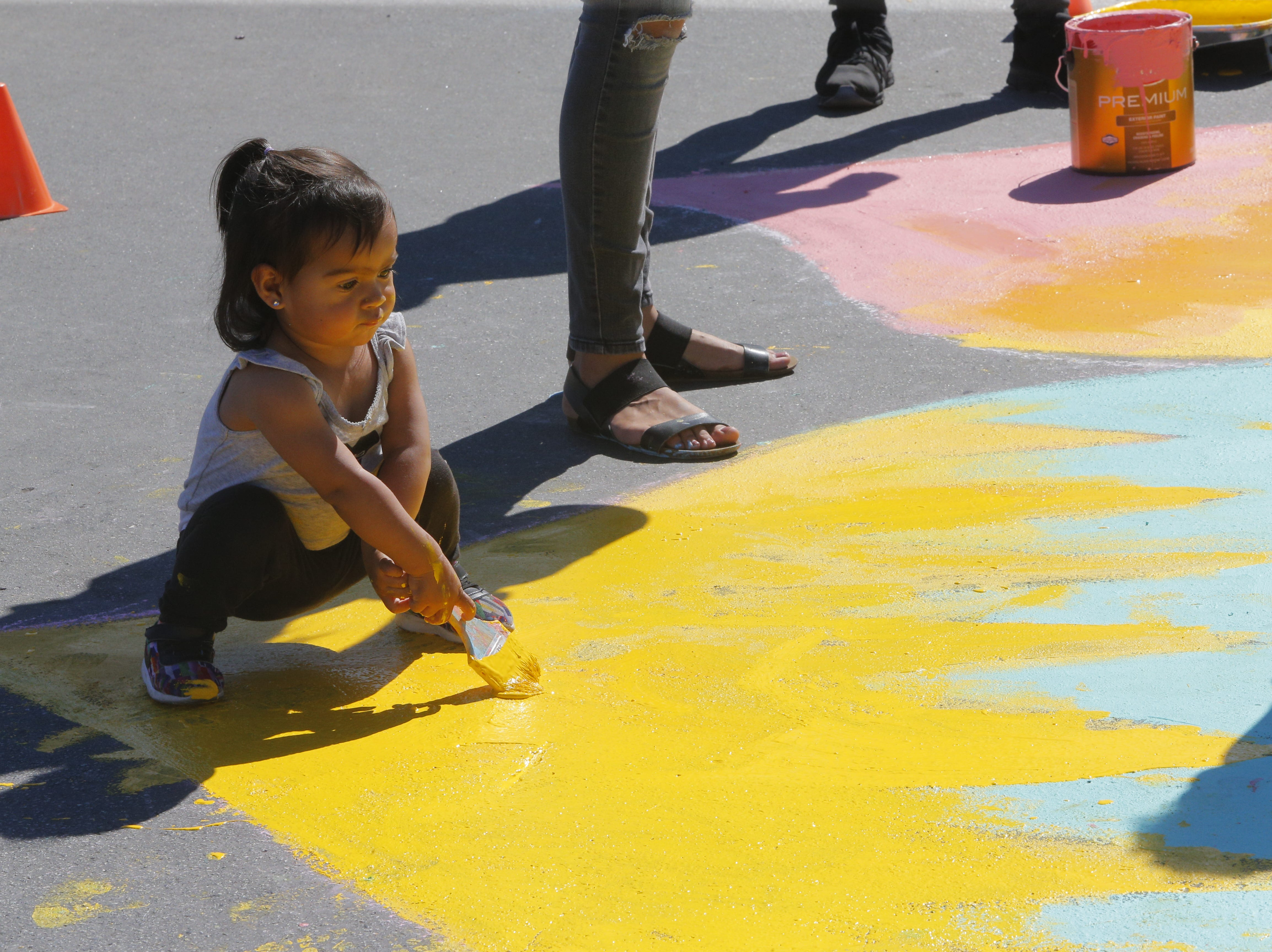 Melanie Garcia, 1, paints the 2018's Ciclovia Salinas Mandala on E. Alisal Street Sunday.