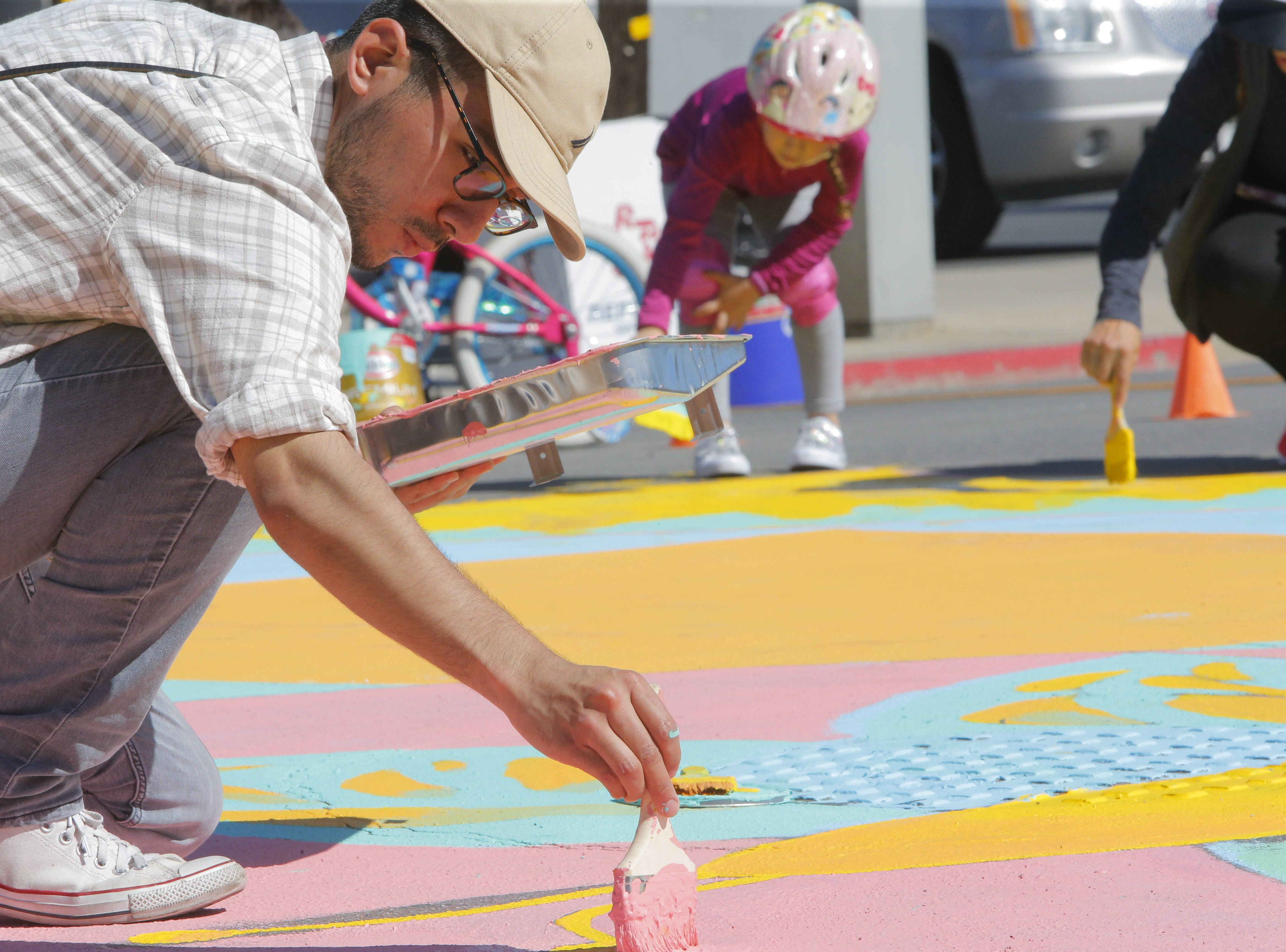 Edwin Carillo paints 2018's Ciclovia Salinas Mandala on E. Alisal Street Sunday.