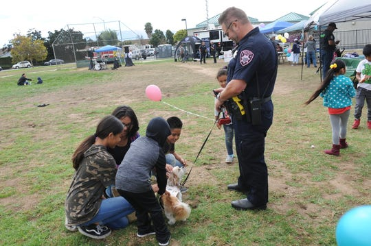 Officer Gabriel Carvey shows off his dog, Buddy, to youths at Saturday's neighborhood block party at Soberanes Park.