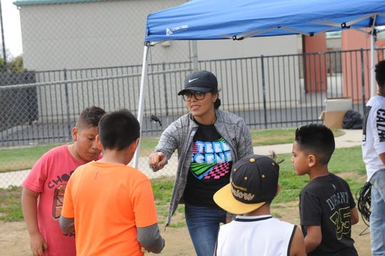 Ana Ambriz hands out prizes to the raffle winner at Saturday's neighborhood block party at Soberanes Park.