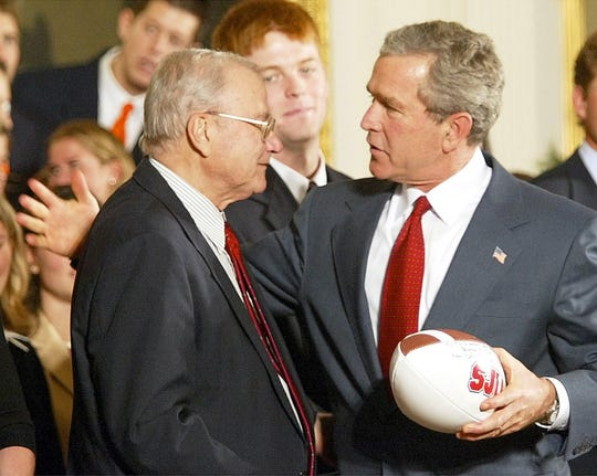President George W. Bush congratulates John Gagliardi on setting the record for the most coaching victories in college football during a ceremony for NCAA Champions in the East Room of the White House,  Nov. 17, 2003.