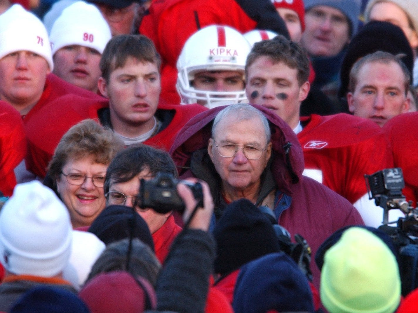 Players and fans surround John Gagliardi after his record-breaking 409th victory against Bethel College in 2003.