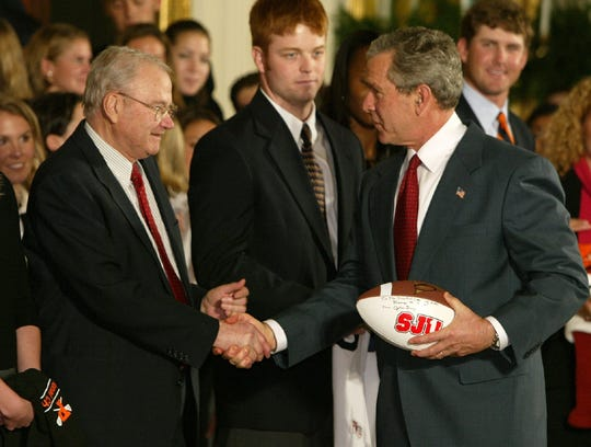 President Bush congratulates Minnesota's St. John's University head football coach John Gagliardi, left, on setting the record for most coaching victories in college football during a ceremony honoring NCAA champions in the East Room of the White House Monday, Nov. 17, 2003. Looking on center is Steve Herce, of the Rice University men's baseball team. (AP Photo/Charles Dharapak)