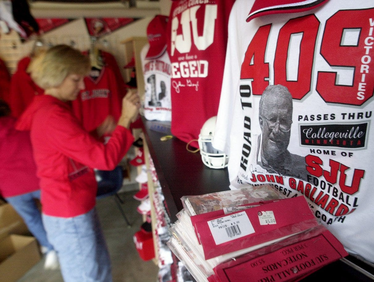 St. John's University Bookstore clothing buyer Mary Kay Kron arranges a line of new John Gagliardi clothing inside the Clemens Stadium store as Gagliardi's 409th win approached.