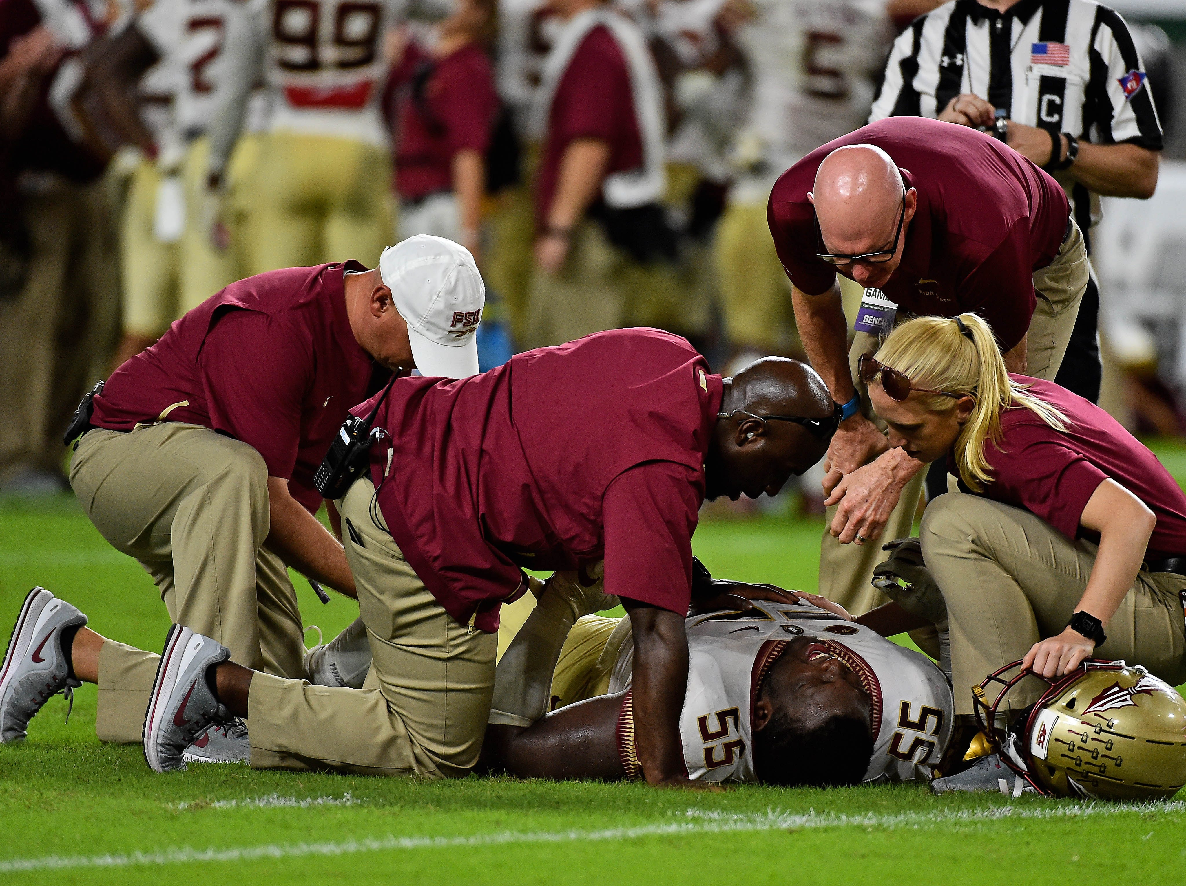 Oct 6, 2018; Miami Gardens, FL, USA; Team trainers attend to Florida State Seminoles defensive tackle Fredrick Jones (55) after being injured during the second half against the Miami Hurricanes at Hard Rock Stadium. Mandatory Credit: Jasen Vinlove-USA TODAY Sports