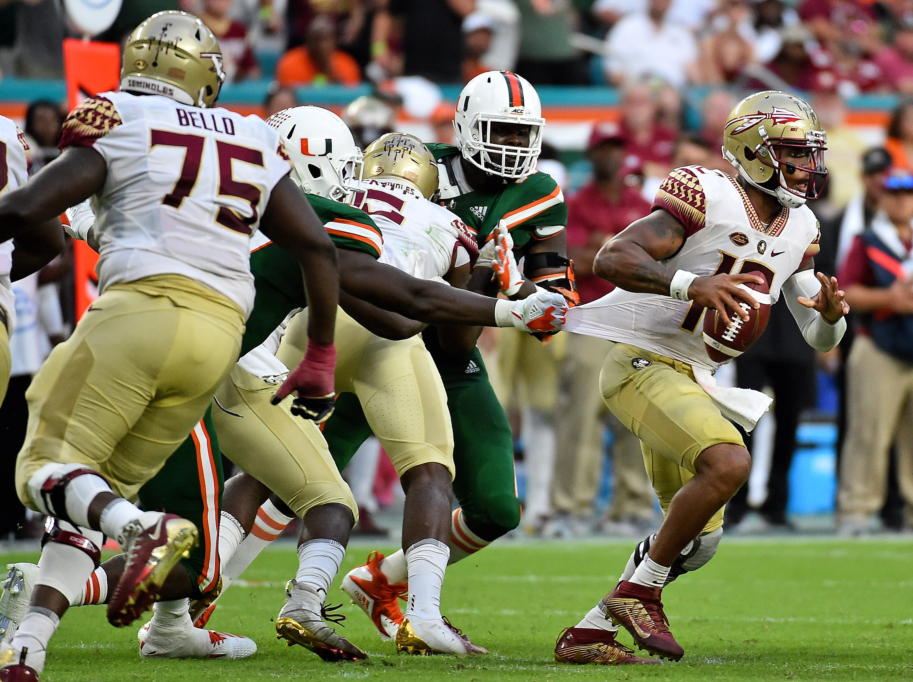 Oct 6, 2018; Miami Gardens, FL, USA; Florida State Seminoles quarterback Deondre Francois (12) runs the ball under pressure during the second half against the Miami Hurricanes at Hard Rock Stadium. Mandatory Credit: Jasen Vinlove-USA TODAY Sports