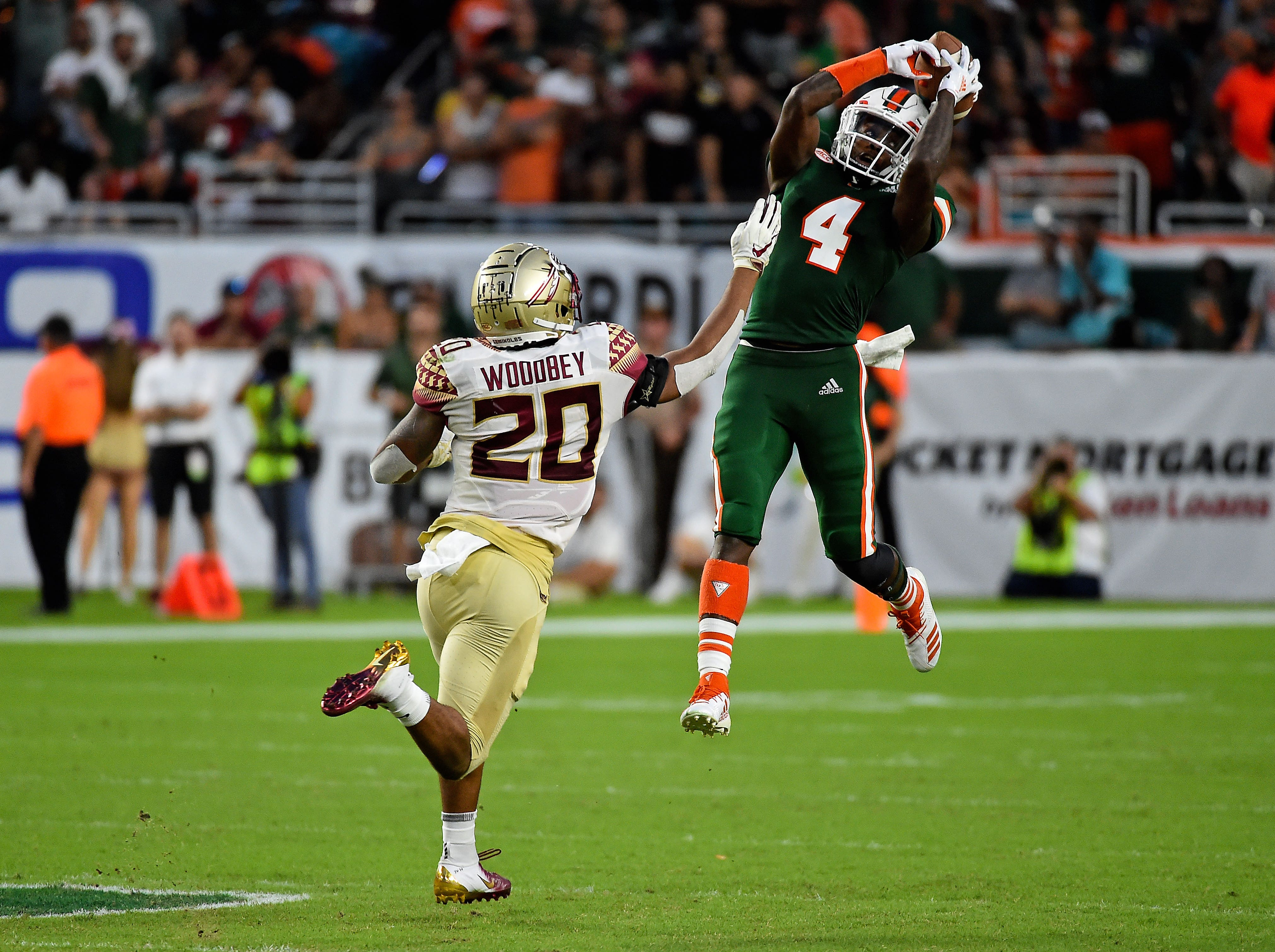Oct 6, 2018; Miami Gardens, FL, USA; Miami Hurricanes wide receiver Jeff Thomas (4) makes a catch over Florida State Seminoles defensive back Jaiden Woodbey (20) during the second half at Hard Rock Stadium. Mandatory Credit: Jasen Vinlove-USA TODAY Sports