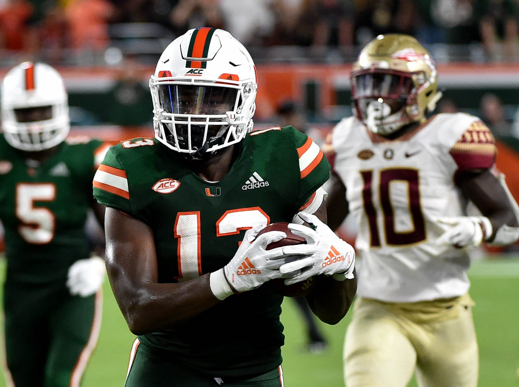 Oct 6, 2018; Miami Gardens, FL, USA; Miami Hurricanes running back DeeJay Dallas (13) carries the ball past Florida State Seminoles defensive back Calvin Brewton (10) during the second half at Hard Rock Stadium. Mandatory Credit: Steve Mitchell-USA TODAY Sports
