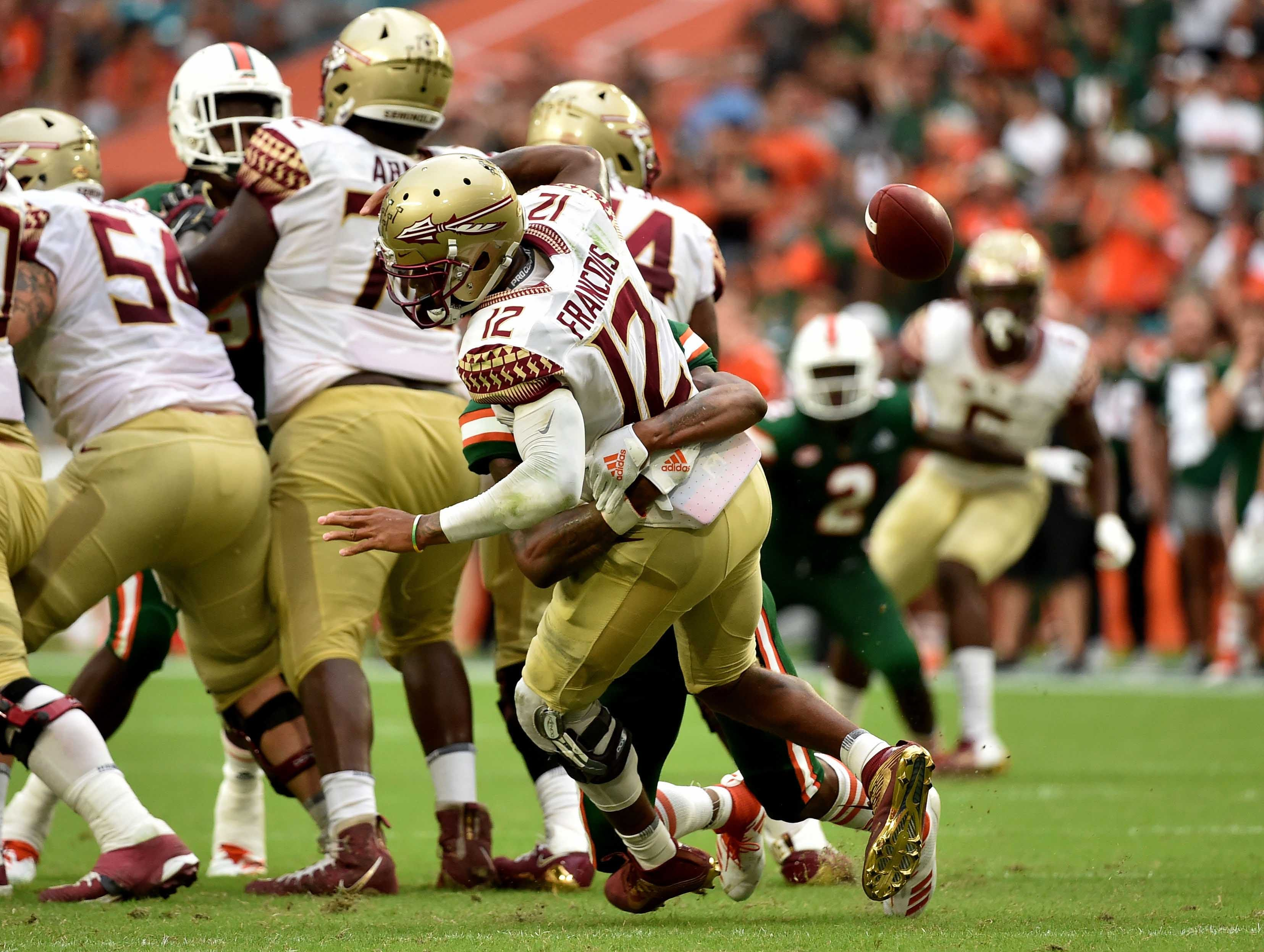 Oct 6, 2018; Miami Gardens, FL, USA; Miami Hurricanes defensive back Sheldrick Redwine (22) sacks Florida State Seminoles quarterback Deondre Francois (12) for a fumble during the second half at Hard Rock Stadium. Mandatory Credit: Steve Mitchell-USA TODAY Sports