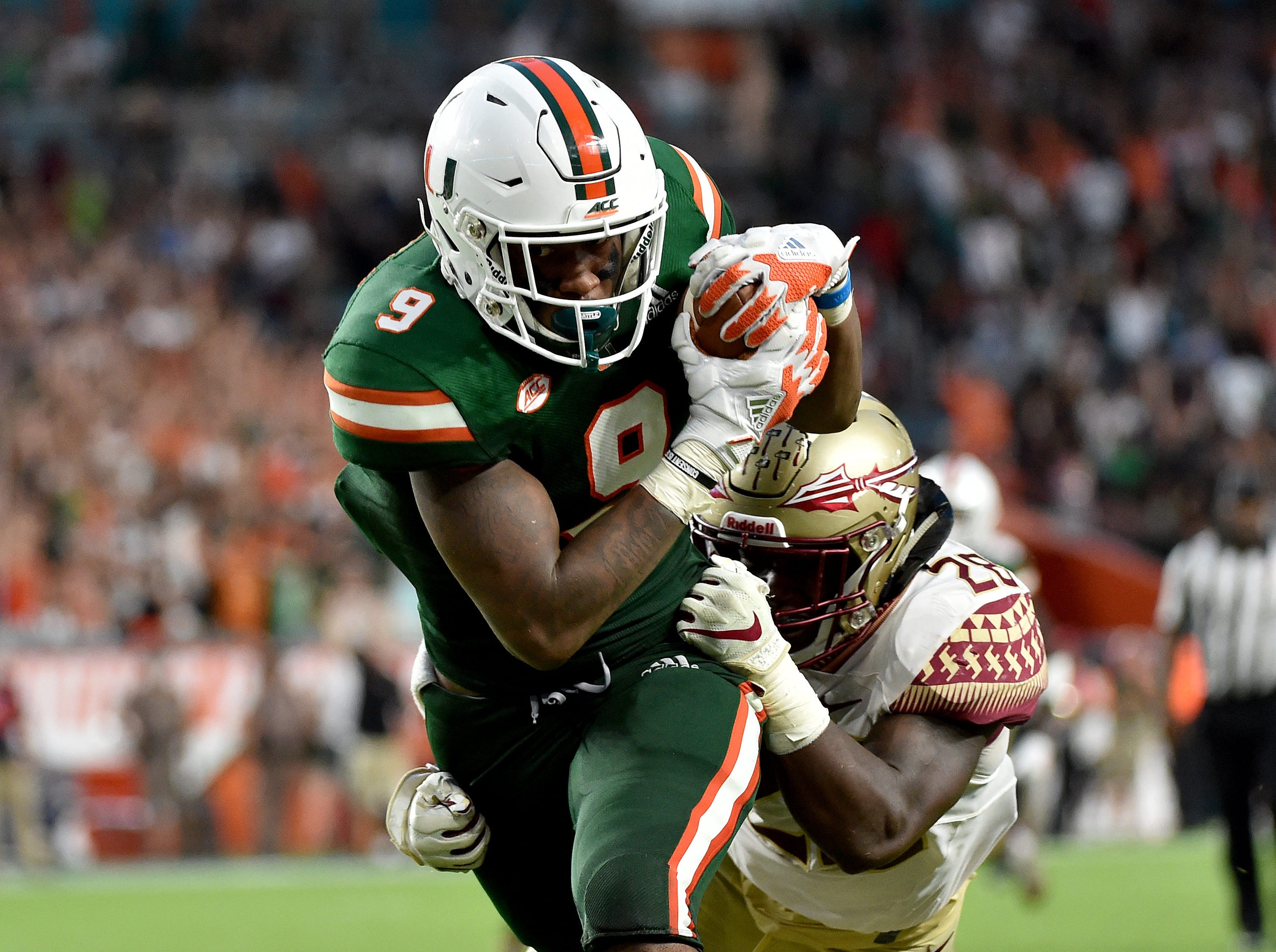 Oct 6, 2018; Miami Gardens, FL, USA; Miami Hurricanes tight end Brevin Jordan (9) runs in a touchdown as Florida State Seminoles linebacker DeCalon Brooks (28) defends the play during the second half at Hard Rock Stadium. Mandatory Credit: Steve Mitchell-USA TODAY Sports