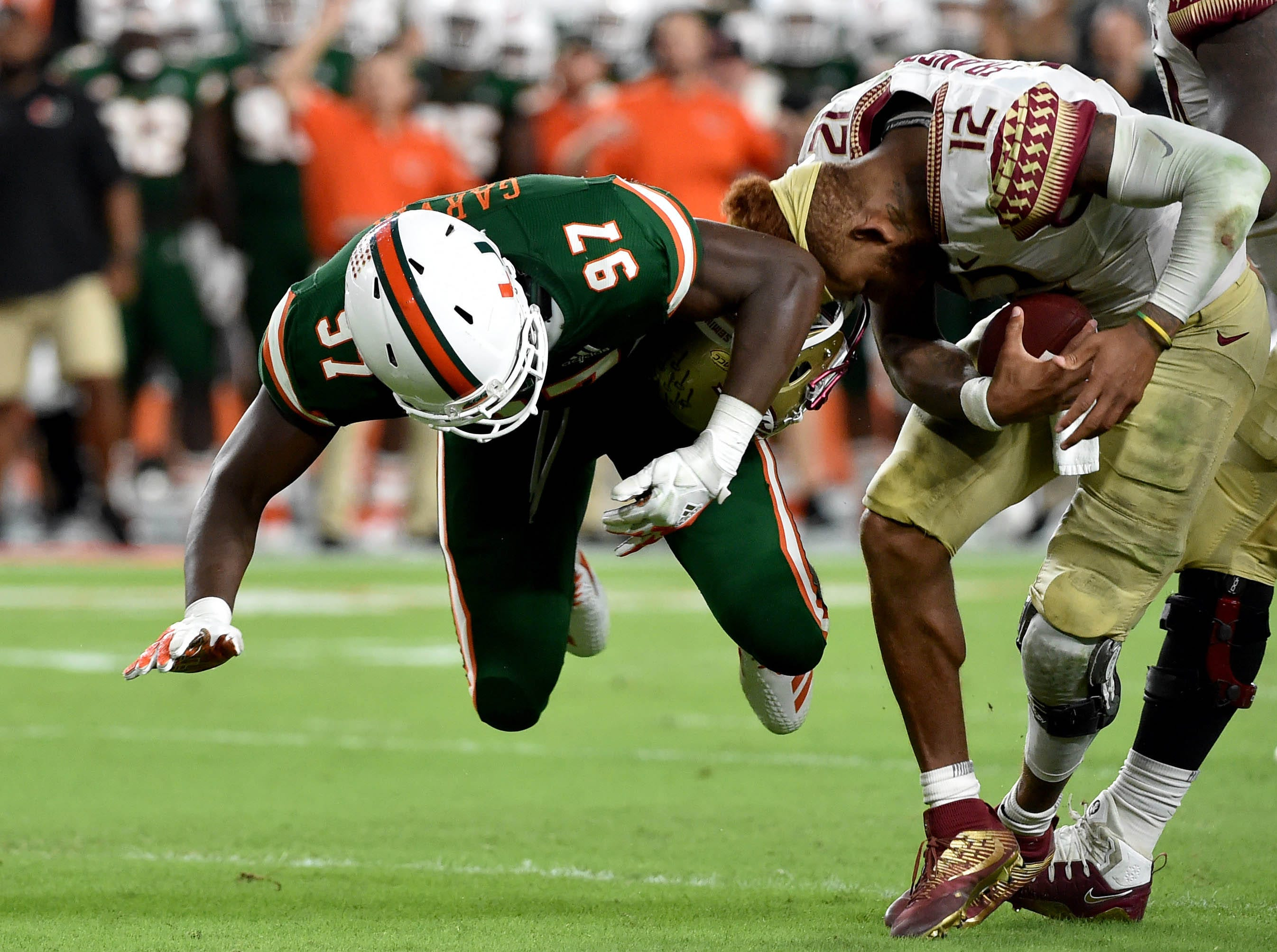 Oct 6, 2018; Miami Gardens, FL, USA; Miami Hurricanes defensive lineman Jonathan Garvin (97) takes the helmet off of Florida State Seminoles quarterback Deondre Francois (12) during the second half at Hard Rock Stadium. Mandatory Credit: Steve Mitchell-USA TODAY Sports