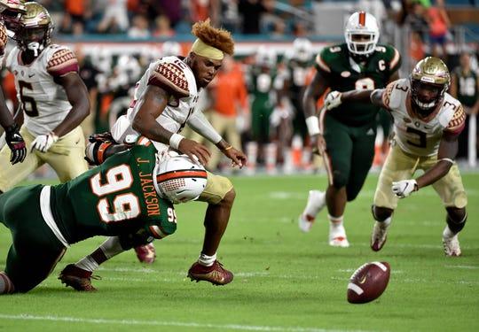 Oct 6, 2018; Miami Gardens, FL, USA; Florida State Seminoles quarterback Deondre Francois (12) loses his helmet as Miami Hurricanes defensive lineman Joe Jackson (99) makes the tackle during the second half at Hard Rock Stadium. Mandatory Credit: Steve Mitchell-USA TODAY Sports