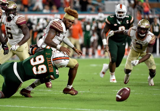 Oct 6, 2018; Miami Gardens, FL, USA; Florida State Seminoles quarterback Deondre Francois (12) loses his helmet as Miami Hurricanes defensive lineman Joe Jackson (99) makes the tackle during the second half at Hard Rock Stadium. Mandatory Credit: Steve Mitchell-USA TODAY Sports