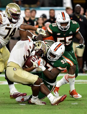 Oct 6, 2018; Miami Gardens, FL, USA; Florida State Seminoles running back Cam Akers (3) is tackled by Miami Hurricanes defensive lineman Jonathan Garvin (97) during the second half at Hard Rock Stadium. Mandatory Credit: Steve Mitchell-USA TODAY Sports