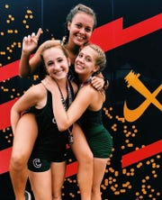 Chiles' Olivia Miller (top), Emily Culley, and Caitlin Wilkey celebrate a team win at the Great American Cross Country Festival in Cary, N.C.