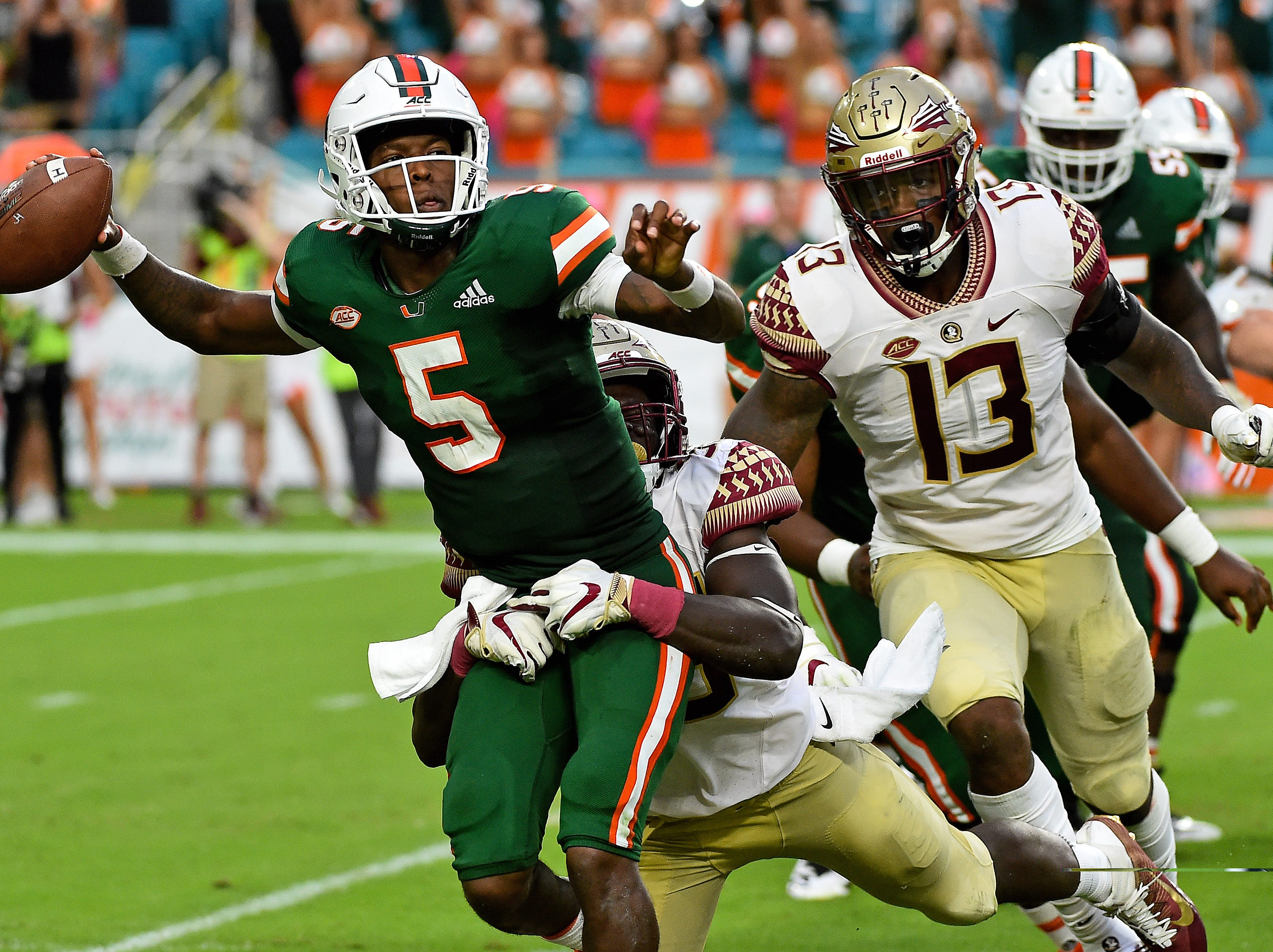 Oct 6, 2018; Miami Gardens, FL, USA; Florida State Seminoles linebacker Leonard Warner III (35) wraps up Miami Hurricanes quarterback N'Kosi Perry (5) during the second half at Hard Rock Stadium. Mandatory Credit: Jasen Vinlove-USA TODAY Sports