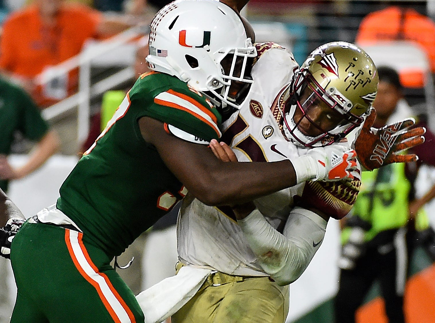 Oct 6, 2018; Miami Gardens, FL, USA; Miami Hurricanes defensive lineman Jonathan Garvin (97) pressures Florida State Seminoles quarterback Deondre Francois (12) during the second half at Hard Rock Stadium. Mandatory Credit: Jasen Vinlove-USA TODAY Sports