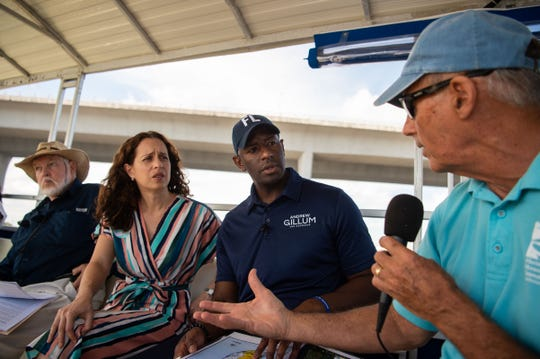 Democratic gubernatorial candidate and Tallahassee Mayor Andrew Gillum (center) listens to Mark Perry, executive director of the Florida Oceanographic Society, talk about the blue-green algae crisis during a boat tour on the St. Lucie River on Sunday, Oct. 7, 2018, out of Shepard Park in Stuart. Democratic candidate Lauren Baer (left of center) — challenging incumbent U.S. Rep. Brian Mast — was also on the boat, and later attended a rally organized by democrats where Gillum addressed a crowd of more than 1,000 people at Memorial Park in downtown Stuart. Pictured at left, R. Grant Gilmore Jr., senior scientist and president at Estuarine, Coastal and Ocean Science Inc., prepares to talk about the impacts on wildlife in the Indian River Lagoon.