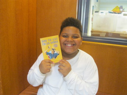Elijah Valentin, 9, shows off the gift book he received for being the top food donor at the library this summer.