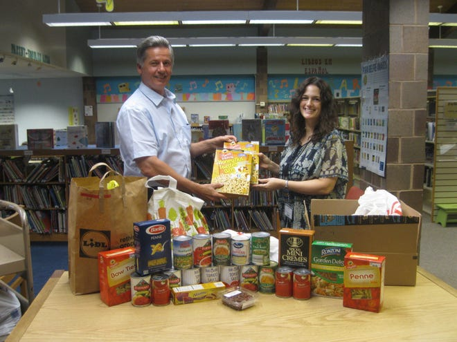 Alex Kaganzev (left) receives non-perishable food items collected at the library this summer from Head of Children's and Young Adult Services Helen Cowan Margiotti.