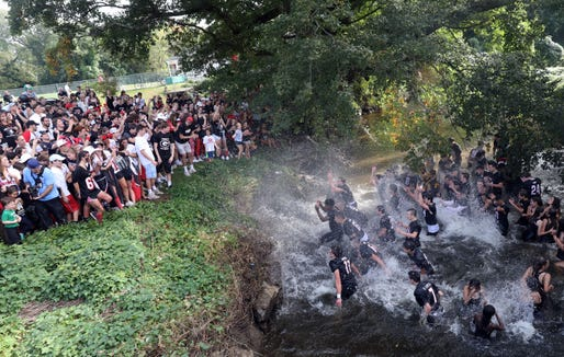 The Rye Garnets football team celebrate in a creek after their 41-14 victory over rival Harrison Huskies Oct. 7, 2018 at Rye High School. Rye won, 41-14.