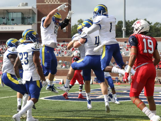 Delaware's Colby Reeder (4) is the center of attention after he scored on a strip of a Richmond receiver. His fumble return from 34 yards out  gave the Hens a 16-0 lead in 5:08 of game time.