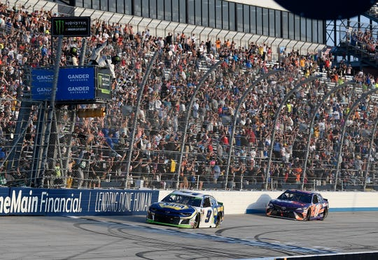 Chase Elliott (9) takes the checkered flag in front of Denny Hamlin (11) to win a NASCAR Cup Series auto race, Sunday, Oct. 7, 2018, at Dover International Speedway in Dover, Del. (AP Photo/Nick Wass)