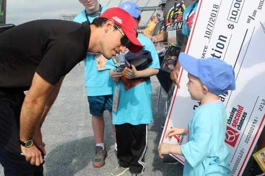 NASCAR driver Joey Logano talks to one of the eight B+ Foundation children with cancer near the Monster Mile garage at Dover International Speedway.