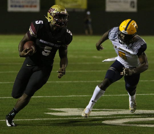 Midwestern State's Adrian Seales runs by Texas A&M-Commerce's Kader Kohou Saturday, Oct. 6, 2018, at Memorial Stadium.