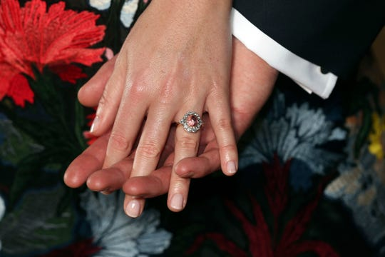 Princess Eugenie shows off her ring, a padparadscha sapphire surrounded by diamonds, as she posed with Jack Brooksbank in the Picture Gallery at Buckingham Palace after they announced their engagement on Jan. 22, 2018.
