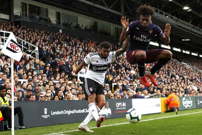 Fulham's Cyrus Christie vies with Arsenal's Danny Welbeck during the English Premier League football match between Fulham and Arsenal at Craven Cottage in London.