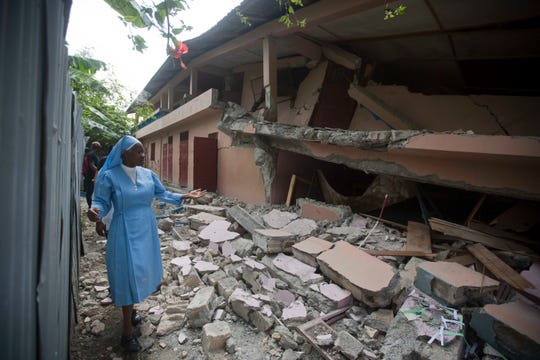 Sister Maryse Alsaint walks alongside a school damaged by a magnitude 5.9 earthquake the night before, in Gros Morne, Haiti, Sunday, Oct. 7, 2018. Emergency teams worked to provide relief in Haiti on Sunday after the quake killed at least 11 people and left dozens injured.