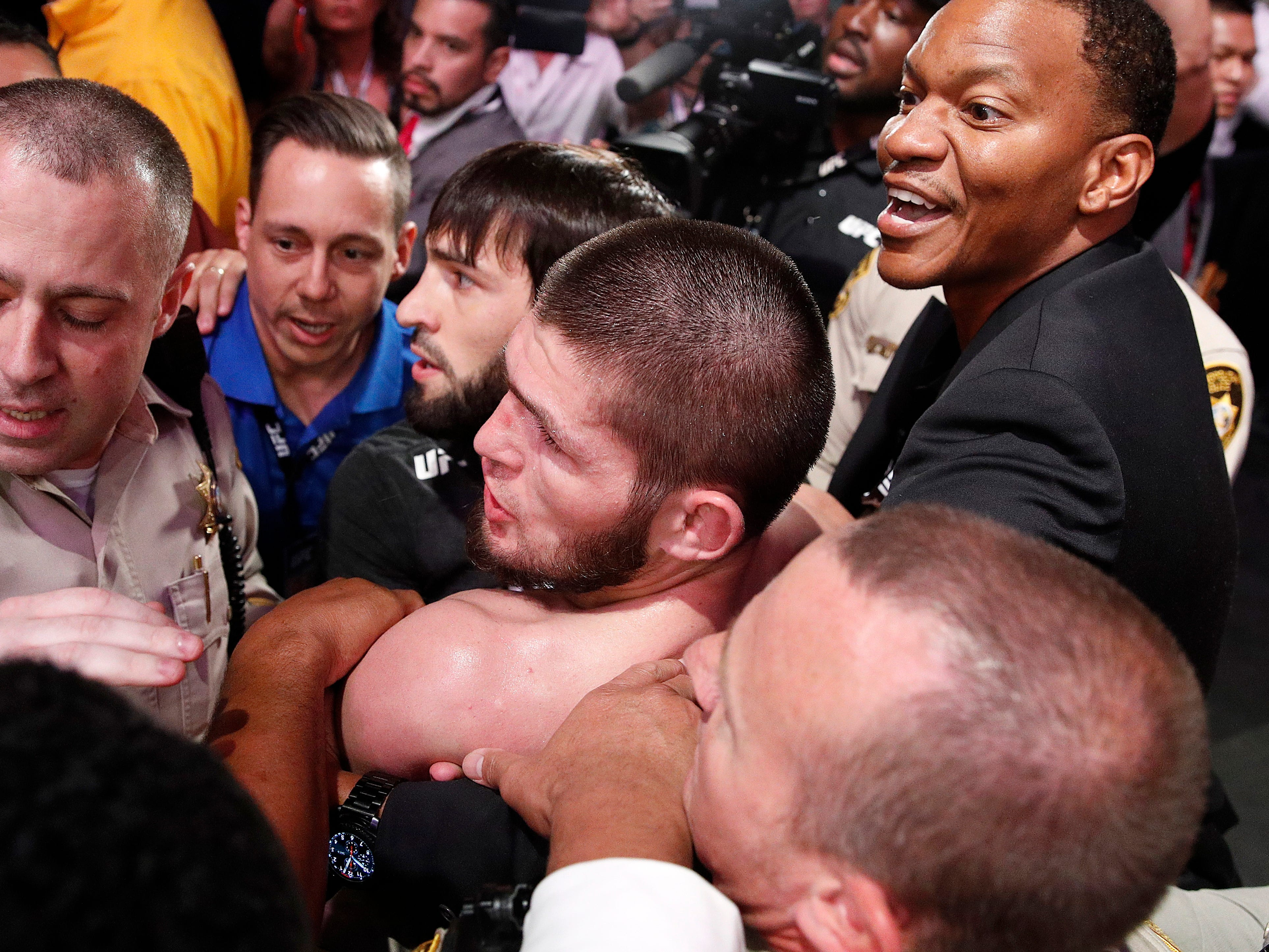 Khabib Nurmagomedov, center, is held back outside of the cage.
