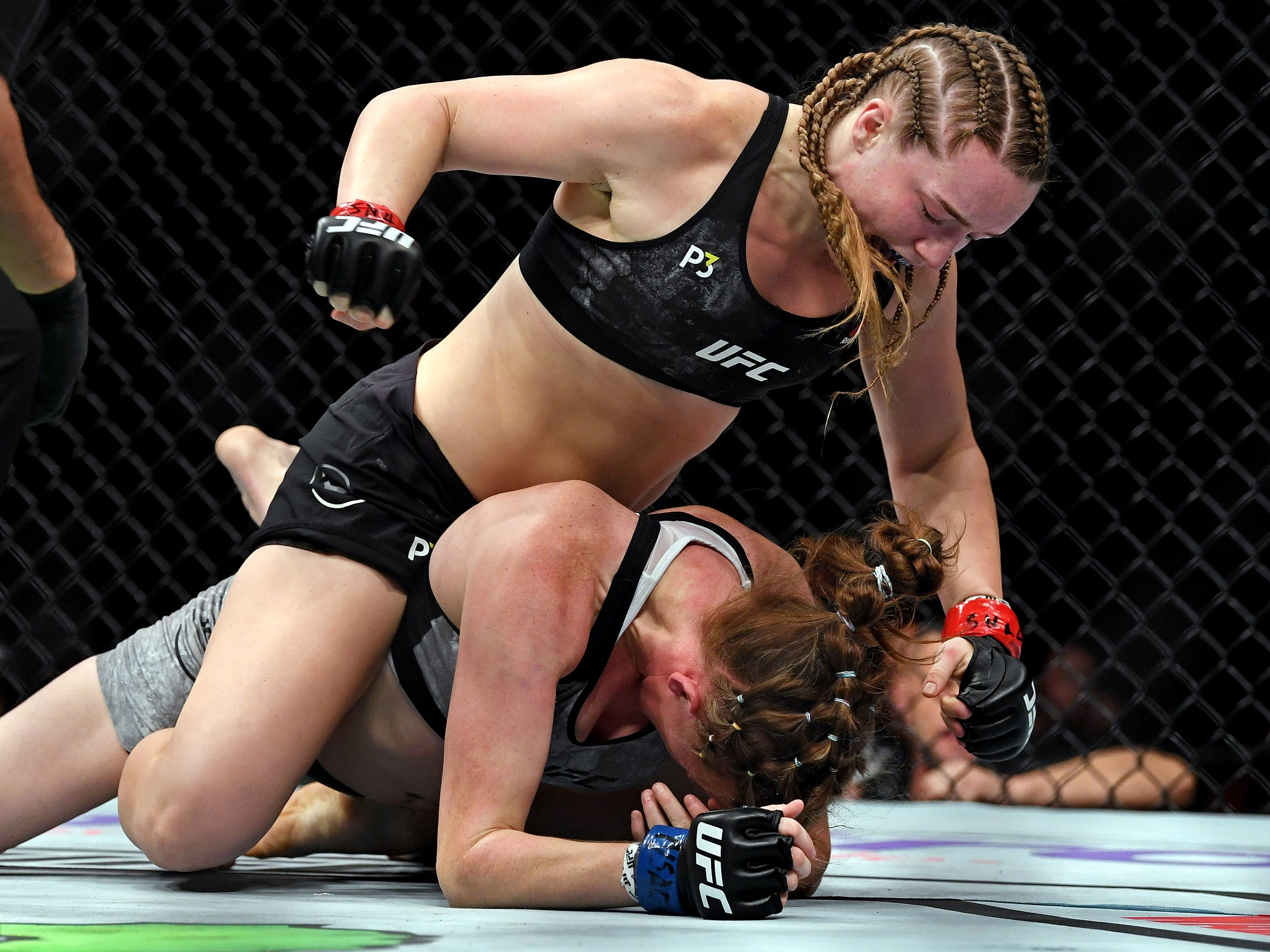 Aspen Ladd, top, pounces on a fallen Tonya Evinger during their bantamweight fight.