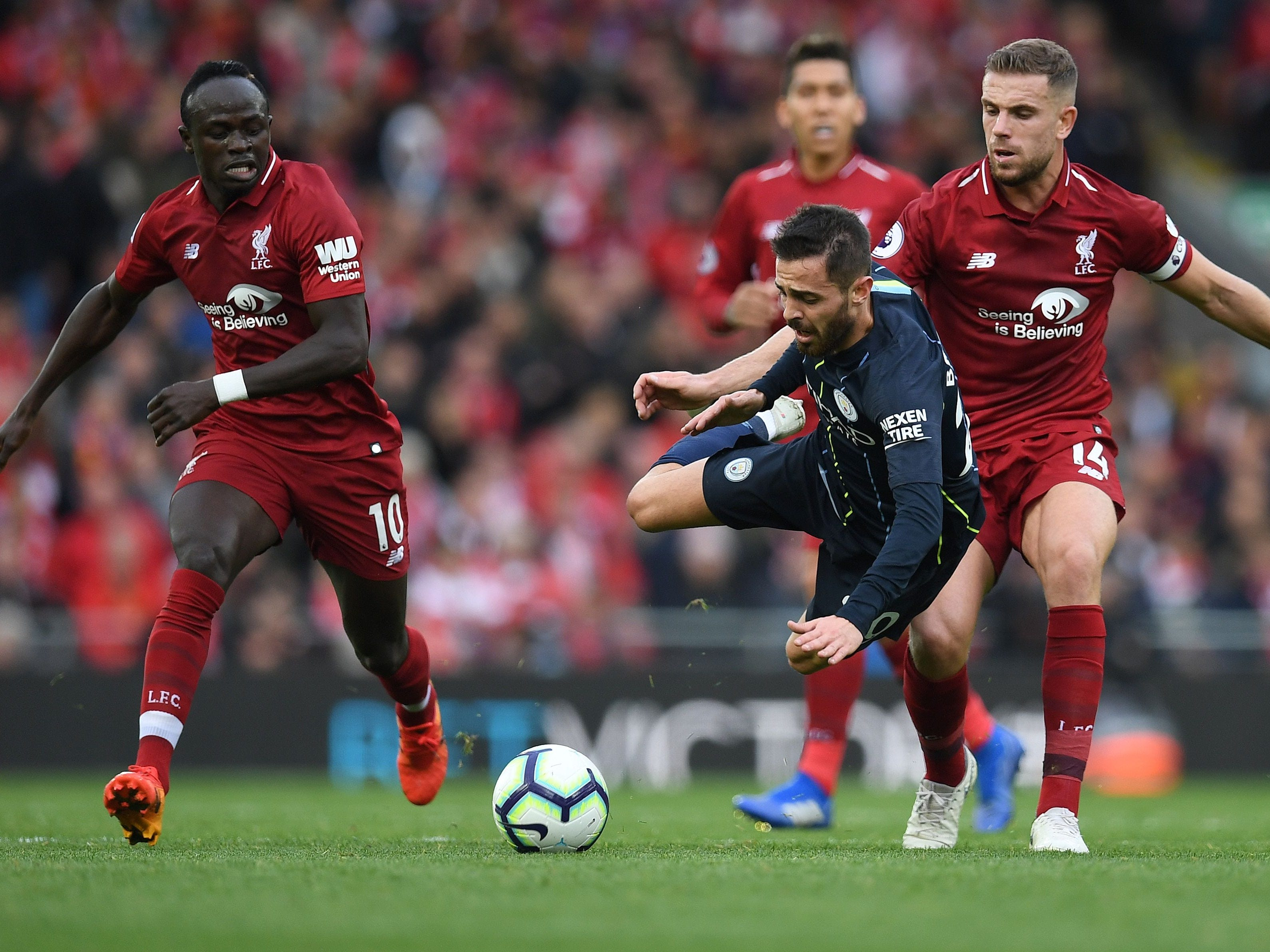 Liverpool's Jordan Henderson vies with Manchester City's Bernardo Silva during the English Premier League football match between Liverpool and Manchester City at Anfield in Liverpool.
