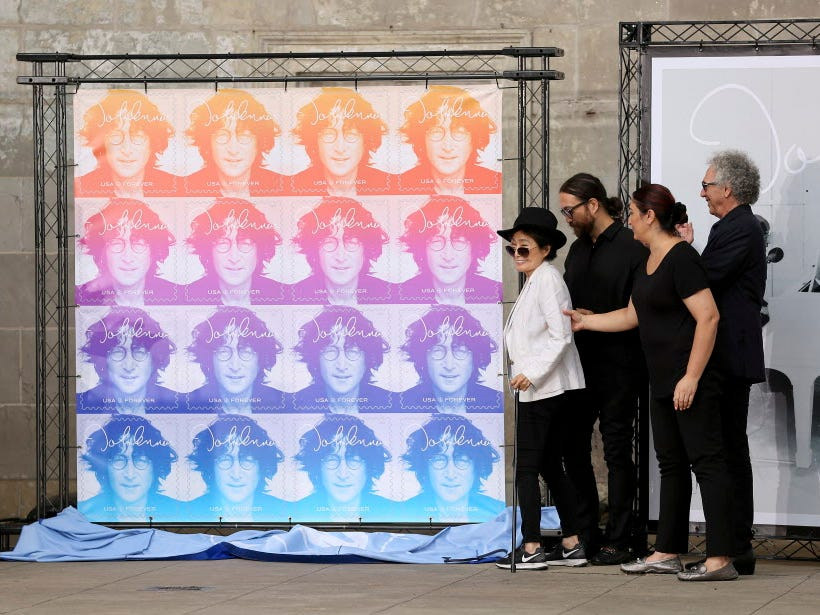 Yoko Ono, fourth from right, unveils the John Lennon Commemorative Forever stamp from the United States Postal Service during a ceremony, Friday, Sept. 7, 2018, in New York. The stamp features a photo of Lennon taken by photographer Bob Gruen, right, that was on the cover of Lennon's 1974 solo album, Walls and Bridges. Also attending the ceremony was Sean Lennon, third from right, radio personality Dennis Elsas, far left, and Postmaster General Megan Brennan, second from left. (AP Photo/Stephen Groves) ORG XMIT: NYR101