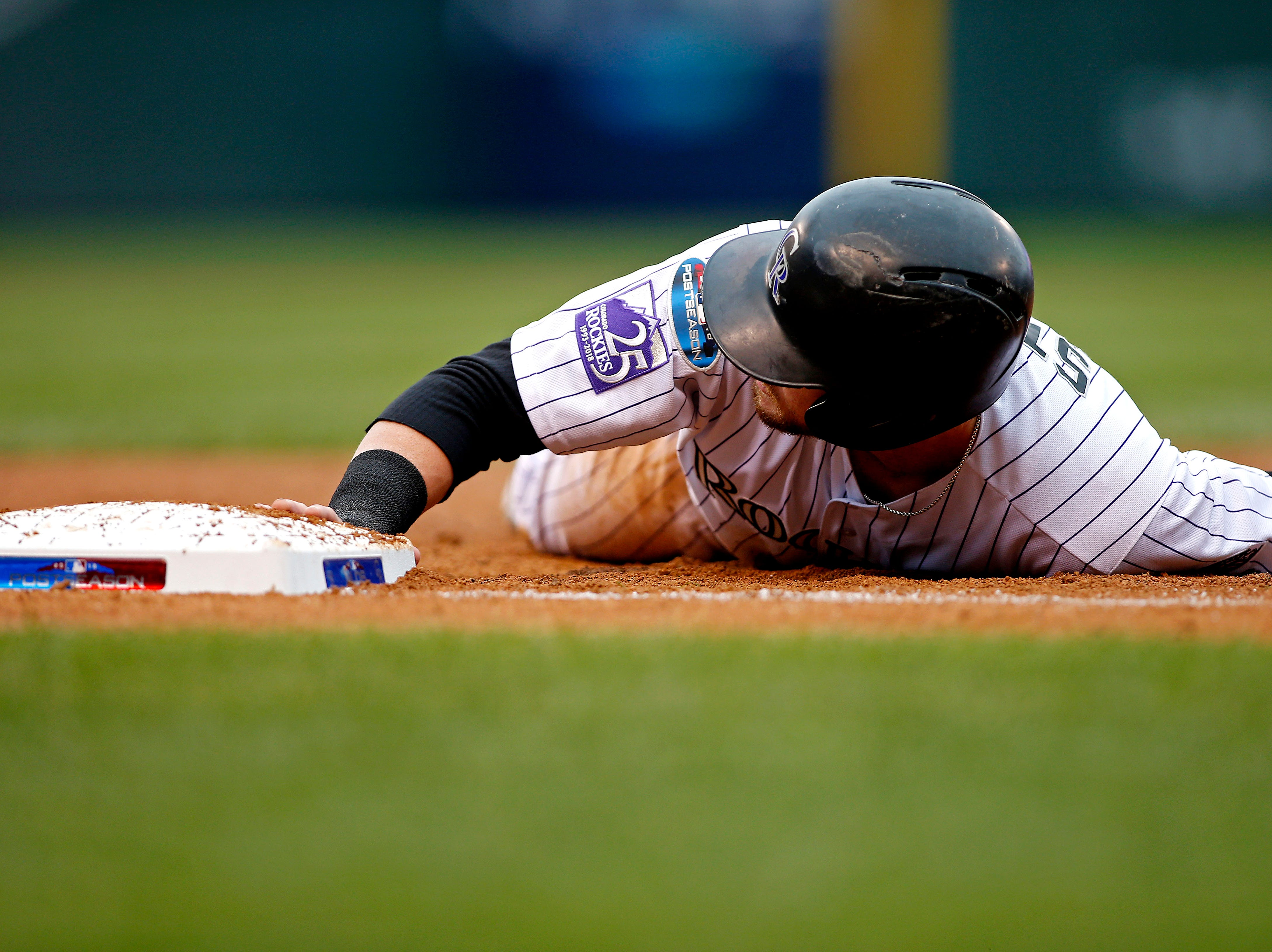 NLDS Game 3: Rockies shortstop Trevor Story dives back to first base in the second inning.