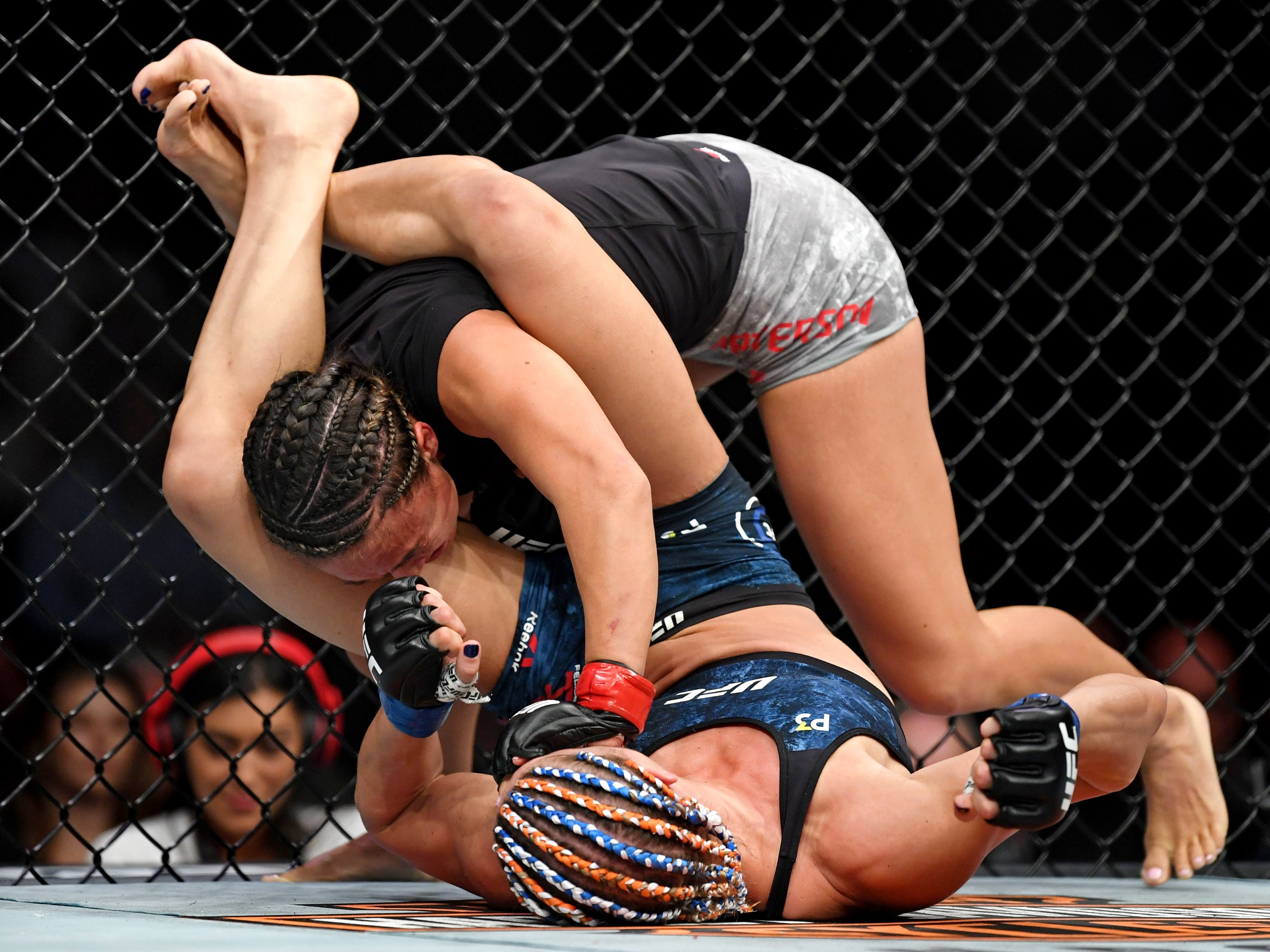 Michelle Waterson, top, grapples for position against Felice Herring.