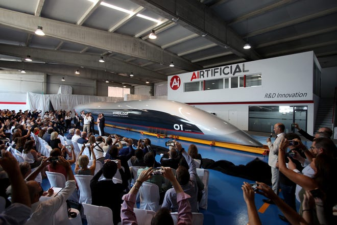 People attend the presentation of the 'Hyperloop' passenger capsule at the Carbures plant at El Puerto de Santa Maria in Spain.  The 'Hyperloop' is the first passenger capsule that will be able to transport passengers at an average speeds up to 750 mph