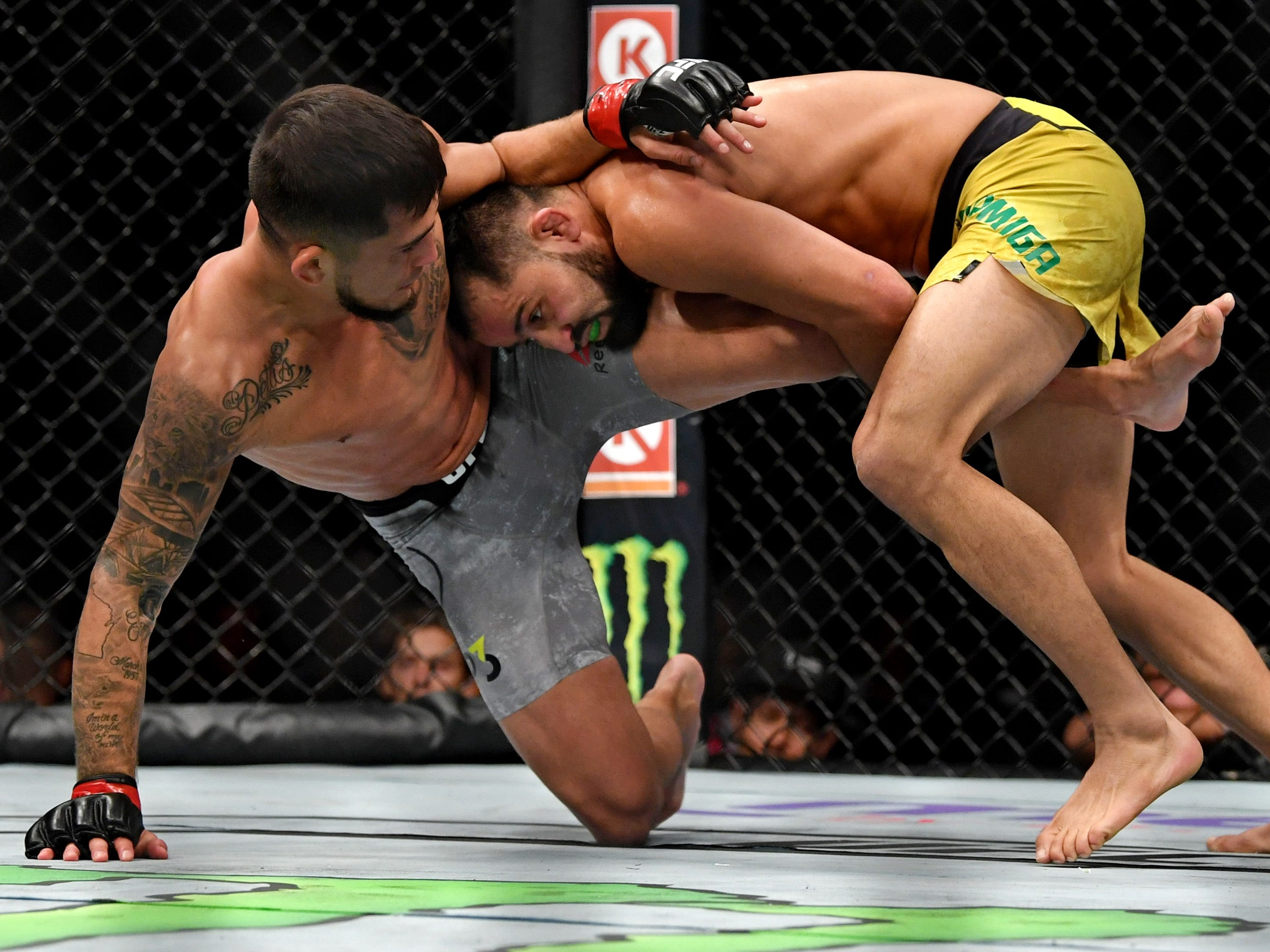 Jussier Formiga , right, takes Sergio Pettis to the mat during their flyweight fight.