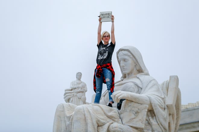 A woman protests on a statue outside the Supreme Court after the Senate voted to confirm Supreme Court nominee Judge Brett Kavanaugh.