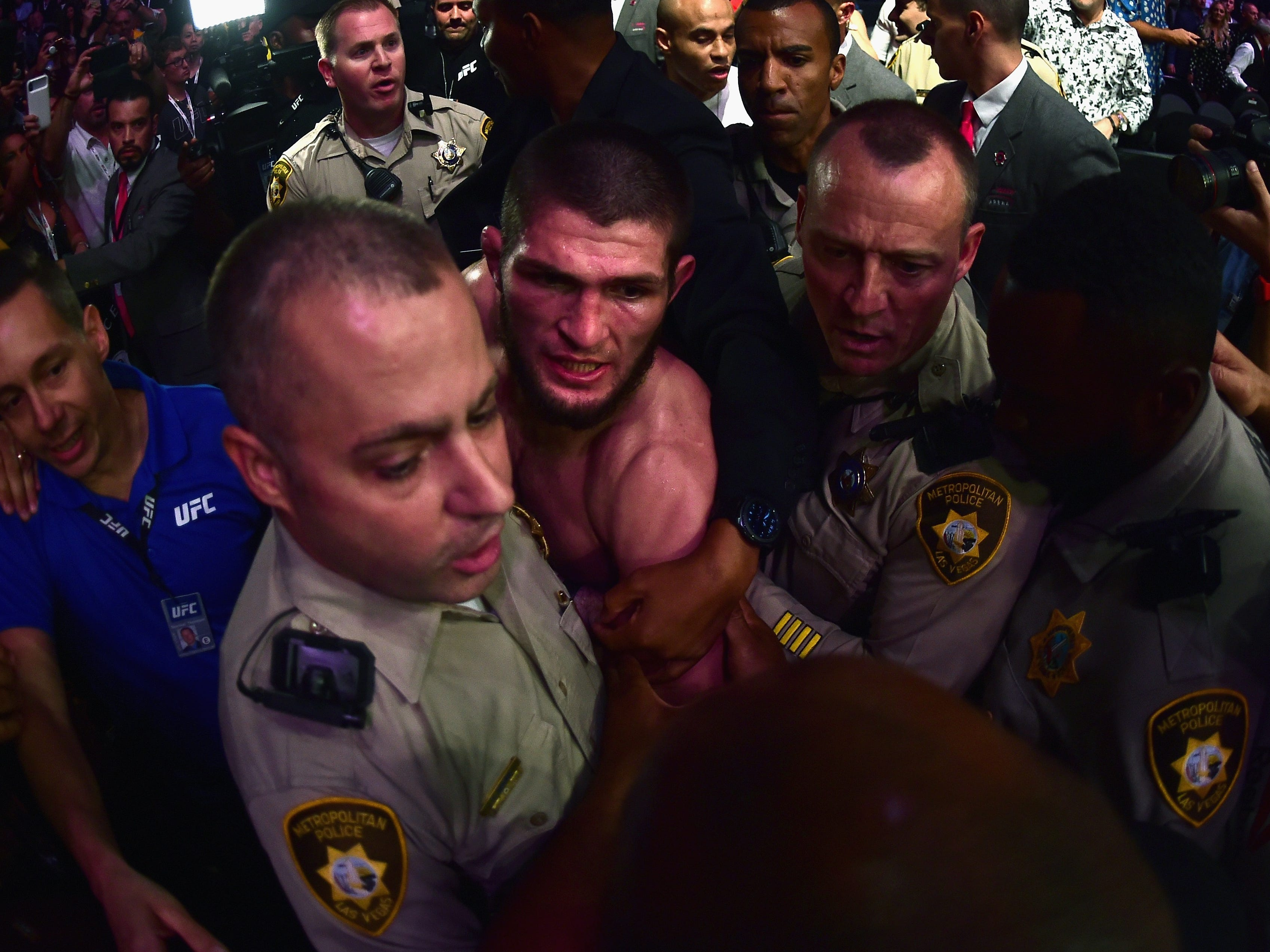 Khabib Nurmagomedov is escorted out of the arena by police and security after the chaotic post-fight scene.