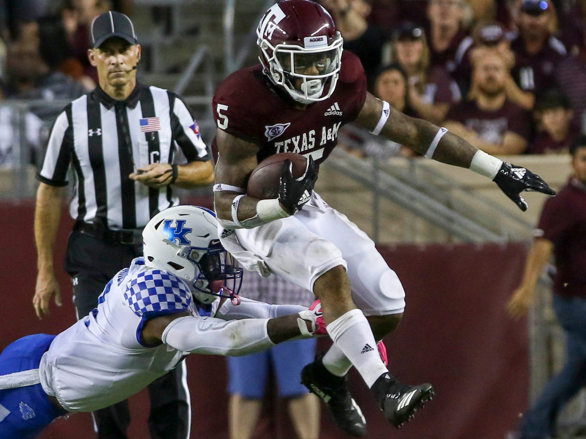 Texas A&M Aggies running back Trayveon Williams (5) evades the tackle of a Kentucky Wildcats defender during the second quarter at Kyle Field.