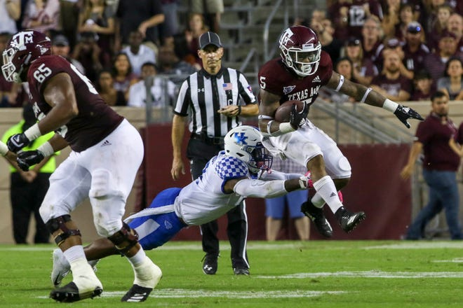 Texas A&M running back Trayveon Williams (5) evades the tackle of a Kentucky defender in the Aggies' 20-14 overtime win over the Wildcats Saturday night in College Station.