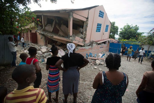 Residents stand looking at a collapsed school damaged by a magnitude 5.9 earthquake the night before, in Gros Morne, Haiti, Sunday, Oct. 7, 2018. Emergency teams worked to provide relief in Haiti on Sunday after the quake killed at least 11 people and left dozens injured.