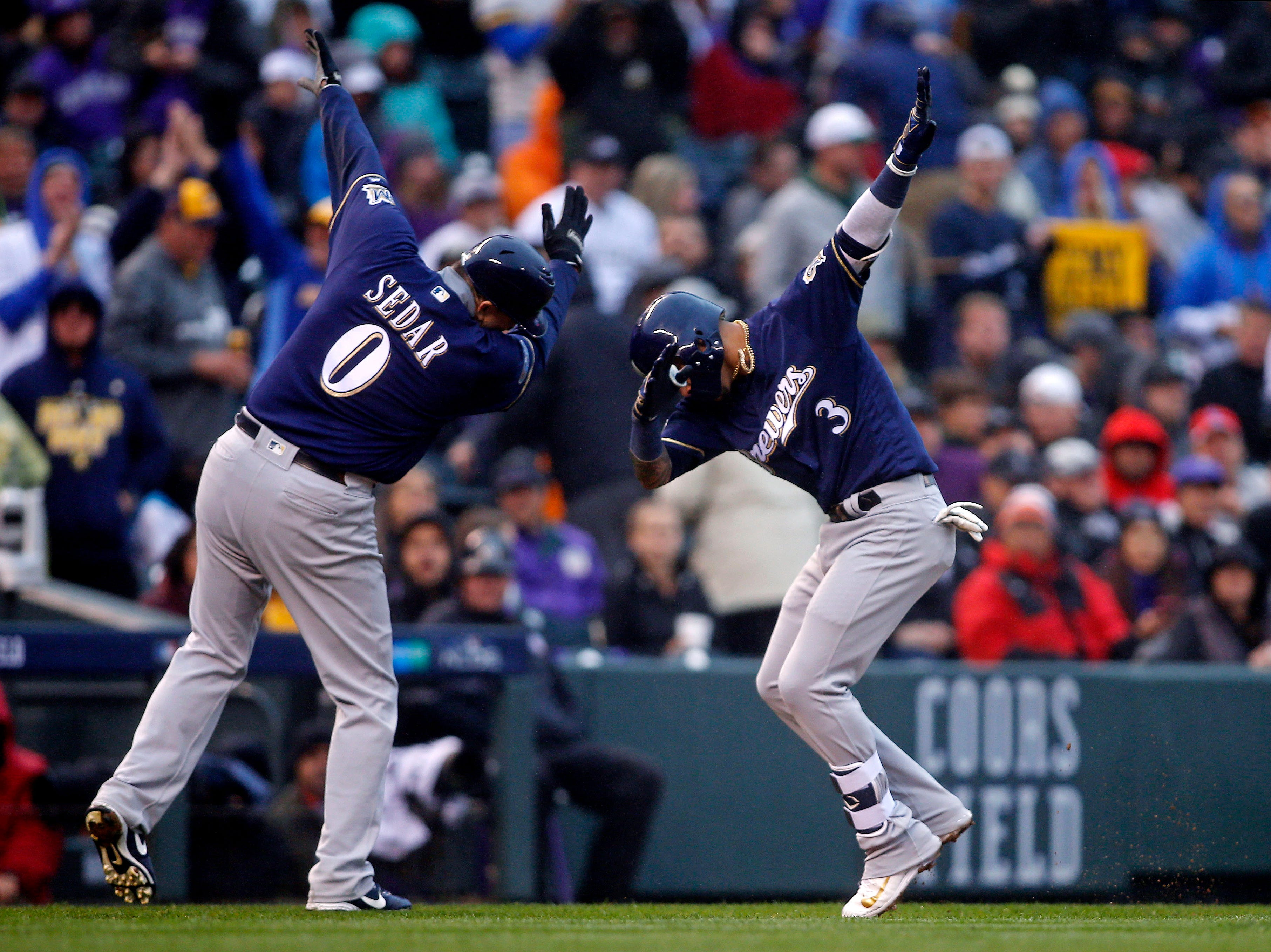 NLDS Game 3: Brewers shortstop Orlando Arcia celebrates his home run in the ninth inning with third base coach Ed Sedar.