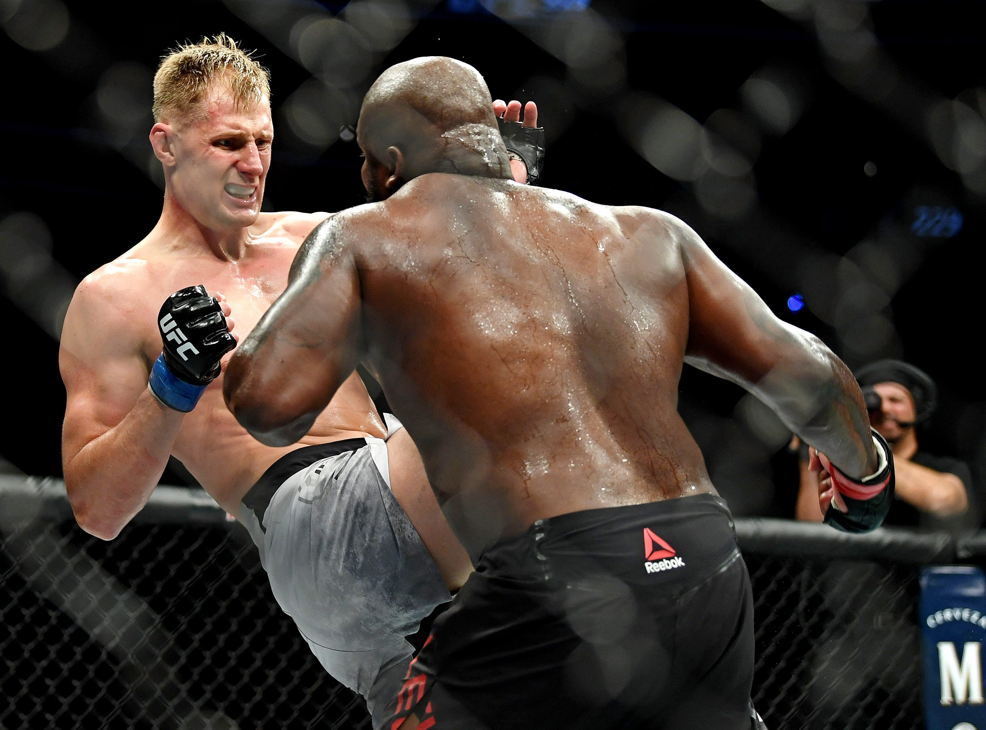 Alexander Volkov, left, throws a kick at Derrick Lewis.
