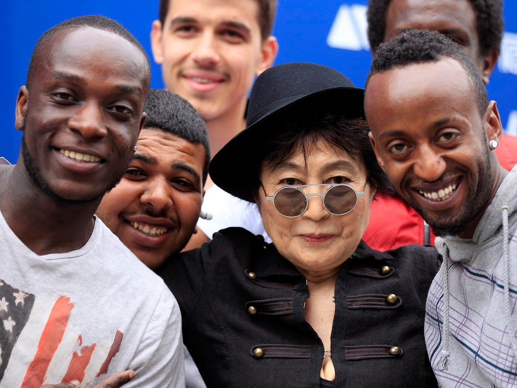 Yoko Ono, center,  joins members of the refugee youth,  from a local charity, for a group photo in front of the John Lennon Educational Tour Bus in London, Tuesday, June 18, 2013.  The bus which houses a mobile recording studio tours Britain and Europe. (AP Photo/Frank Augstein) ORG XMIT: FAS104