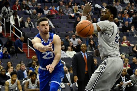 Sandro Mamukelashvili (23) passes around Georgetown Hoyas forward Marcus Derrickson (24)