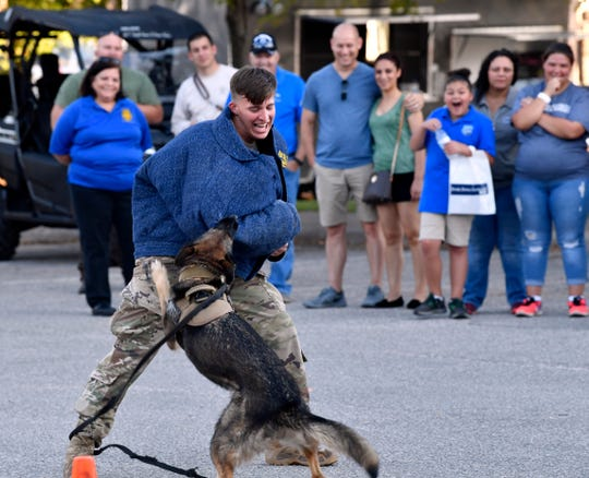 Senior Airman Michael Madeira of the 7th Security Forces Squadron shows how Axa, a military working dog, can take down aggressive subjects. Personnel from Dyess Air Force Base joined Abilene police and fire members for National Night Out on Tuesday. The evening featured free food and demonstrations of equipment.